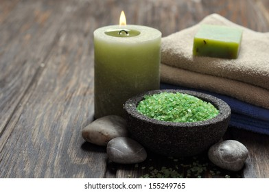 Spa concept. Sea salt in stone bowl with candle and herbal soap