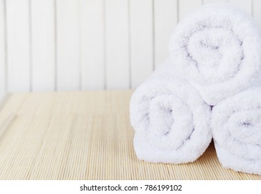 Spa concept: three white fluffy bath towels twisted into a rolls are on a beige bamboo mat, with copy-space