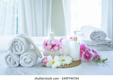 Spa concept. Spa treatment set and aromatic massage oil on bed massage. Thai setting for aroma therapy and massage with flower on the bed, relax and healthy care.