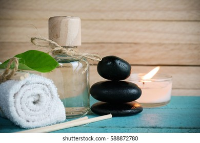 Spa concept. Spa treatments with green leaf, towel, stones and aromatic burning candles on wooden background.