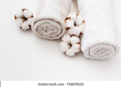 Spa concept. Two  fluffy towels twisted coil and cotton flowers on light white background.