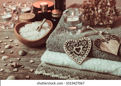 Spa concept in Valentine's Day, candles, handmade heart, dry flower seashells, setting for aroma therapy and salt massage on bed, relax and healthy care. Rustic style. Toned image in chocolate, tones.