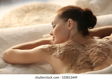 Spa concept. Young woman relaxing on massage desk with nourishing scrub on back