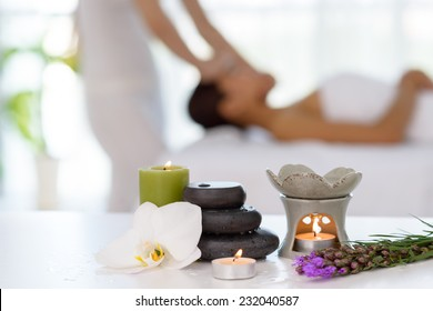 Spa concept: zen stones, candles and flowers on the background of woman receiving treatment