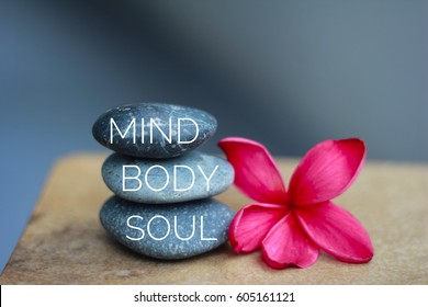 Spa concept of zen stones with deep red plumeria flower. Word Mind body soul.