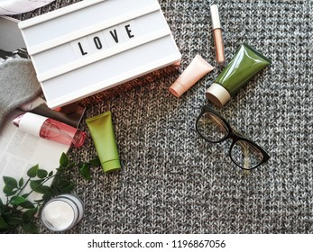 SPA cosmetic products on dark blanket from above. Glasses, magazine, light letterbox, organic creams and serums. Beauty blog flatlay