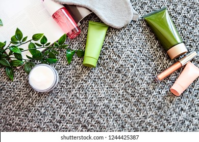 SPA cosmetic products on dark blanket from above. Fashion magazine, organic creams and serums. Beauty blog flatlay