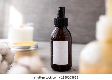 Spa cosmetics in brown glass bottles with white label on gray concrete table. Copy space for text. Beauty blogger, salon therapy, branding mockup, minimalism concept