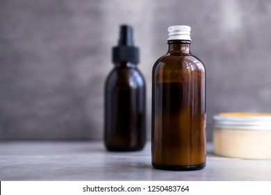 Spa cosmetics in brown glass bottles on gray concrete table. Copy space. Beauty blogger, salon therapy, minimalism concept, vertical