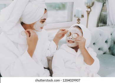 Spa Day in Beauty Salon. Towel on Head. Make Cucumbers Mask. Mom and Daughter in Spa. Consept Beauty Salon. Beautiful Face. Woman and Happy Child. Woman with Curlers. Doing Selfie. Blue Sofa in Salon.