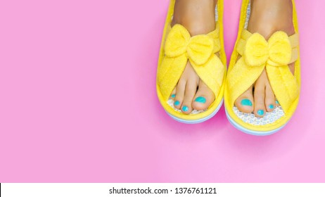 Spa day - perfect holiday for yourself concept.  Bare feet with pedicure and wearing yellow funny slippers over pink background