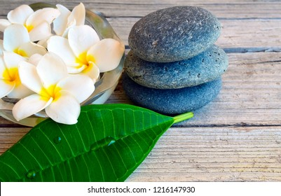 Spa decoration with Frangipani (Plumeria) flowers and zen stones on old wooden background.Relaxing time concept.Selective focus.