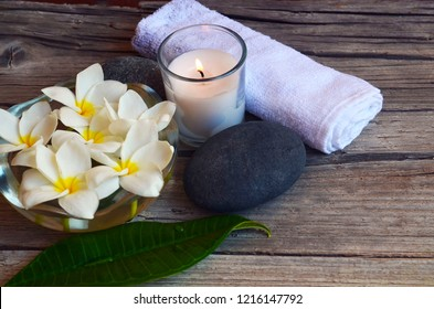 Spa decoration with Frangipani (Plumeria) flowers,zen stone, candle, salt in bowl  and towel on old wooden background.Relaxing time concept. Selective focus.