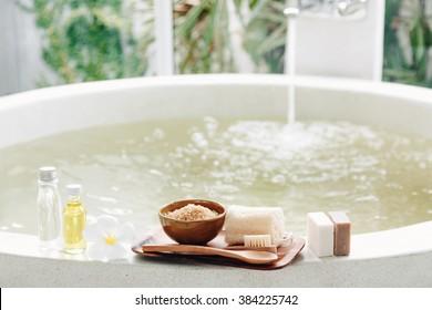 Spa decoration, natural organic products on a bathtube. Loofah, towel and frangipani flower