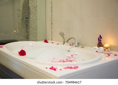 Spa decoration, natural organic products on a bathtube. Loofah, towel, candle and  flower