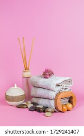 Spa essentials, aroma sticks stones, towels and a plant on a pink background
