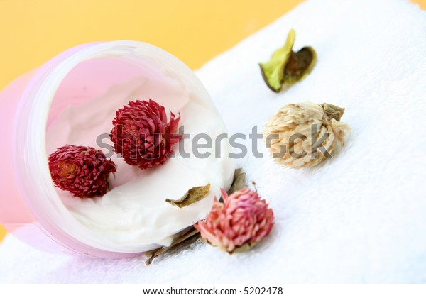 Spa essentials (cream, white towel and pink flowers) isolated on yellow