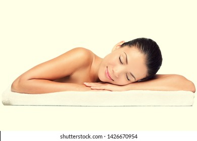 Spa. Face skincare beauty woman smiling happy. Beautiful attractive mixed race Chinese Asian / Caucasian female model lying down on towel during skin care treatment with yellow color filter.