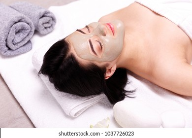 Spa facial mask application. Beautiful relaxed woman having clay face mask in the spa
