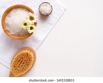 Spa flatlay composition. Sea salt, bath towel, massage wooden brush, flower on white background. Copyspace, top view. Home care concept, relax and rest