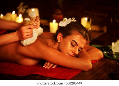 Spa gifts of woman massage in spa salon. Girl on candles background in massage spa salon. Luxary interior in oriental therapy salon. Close up of female massage hands give herbs hot ball therapy. Group
