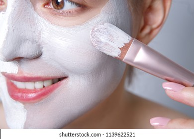 Spa girl applying face mask. Aesthetic procedure. The girl applies an anti-aging mask of clay on the face with a brush. Close view