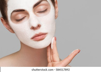 Spa girl applying facial mask. Beauty treatments.