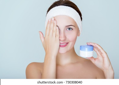 Spa girl with clean perfect skin and head, bandage holding of cream or scrub, naked shoulders