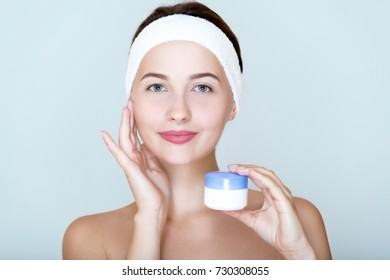 Spa girl with clean perfect skin and head, bandage holding of cream or scrub, naked shoulders.