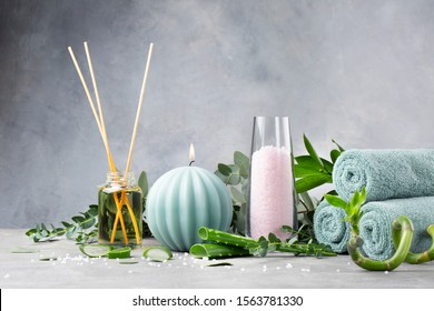 Spa green concept. Burning candle, oil, lavender sea salt, aloe Vera, towels and eucalyptus on a gray background