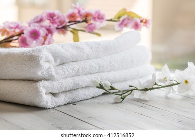 Spa hotel and resort - Towels and flowers on a white wooden table