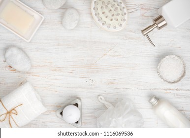 Spa items and cosmetics on wood, copy space in center