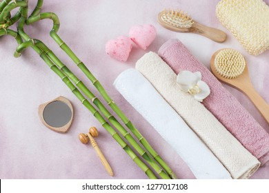 Spa items on a pink background: towels, sea salt, bamboo, brushes, washcloth and soap in the form of two pink hearts