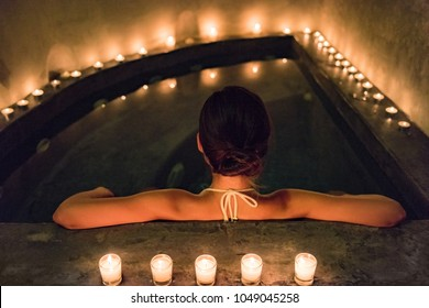 Spa luxury jacuzzi woman relaxing in whirlpool hot tub with water massaging jets. Woman in candlelight enjoying hydrotherapy in private massage pool. Hotel lifestyle.