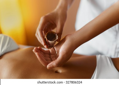Spa massage. Aromatherapy oil massage. Masseur doing aromatherapy oil massage on beautiful young healthy caucasian woman body in spa salon.  Skincare, wellbeing, wellness, lifestyle.