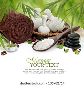 Spa massage border background with rolled towel, compress balls, stacked basalt stones, sea salt, and bamboo