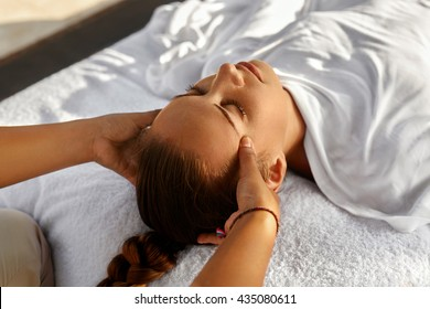 Spa Massage. Masseur Hand Massaging Girl's Head With Aromatherapy Oil. Closeup Of Beautiful Healthy Happy Woman Relaxing In Day Spa Salon Outdoors. Relax Beauty Body Care Treatment Concept