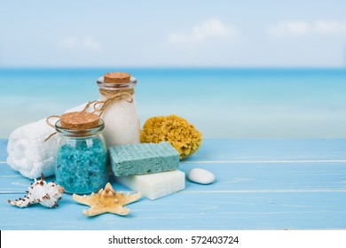 Spa massage products on wood over blurred blue sea background