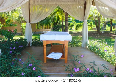 Spa massage room at beachside in bungalow, massage tables with towels. Beauty care concept. Spa beds ready to massage at outdoors tropical island resort.