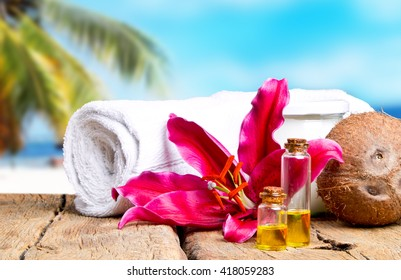 spa massage setting with lilium, oil, towel and salt on wood with tropical beach background