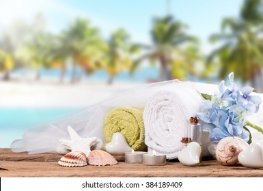 Spa and massage setting on wood with tropical beach background