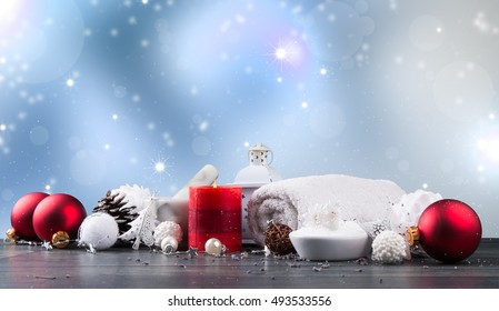 spa massage setting, product, oil and christmas decoration on wooden background, Christmas wellness concept