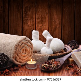 Spa massage setting with thai herbal compress stamps and candlelight