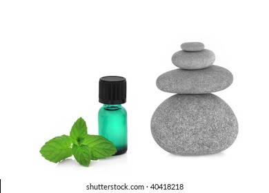 Spa massage treatment stones in perfect balance with peppermint herb leaf sprig and aromatherapy essential oil dropper bottle, over white background.