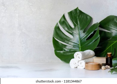 Spa and massage treatments on white, marble background monstera leaves. Flat lay. Top view