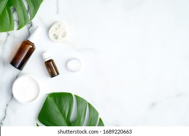 SPA natural organic cosmetic products with monstera tropical plant leaves on marble background. Flat lay, top view, copy space. Skin care and beauty treatment concept