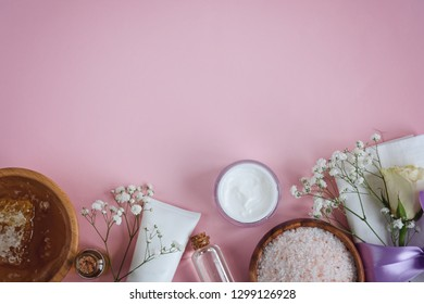 Spa natural skin care products on pink background, cosmetic products - cream, oil and honey creative layout