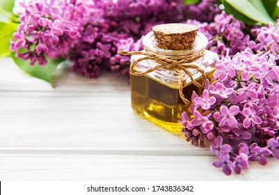 Spa oil with lilac flowers. Bottle with aroma oil  and lilac flowers on wooden background.