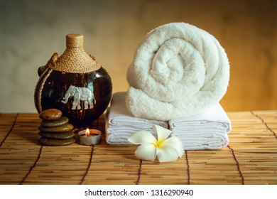 Spa Oil Massaging Treatment and Skincare Concept., Component of Therapy Massage With Plumeria or Frangipani Flowers, Towel, Stones, Aroma Candle and Oil on The Desk.