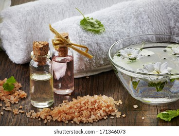 Spa oils and sea salt on wooden table